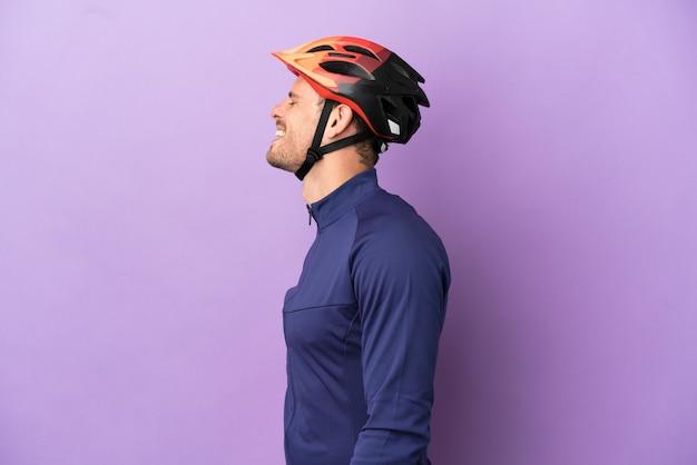 Молодой бразильский велосипедист, изолированные на фиолетовом фоне, смеется в боковом положении