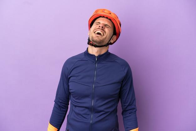 Молодой бразильский велосипедист человек изолирован на фиолетовом фоне смеясь