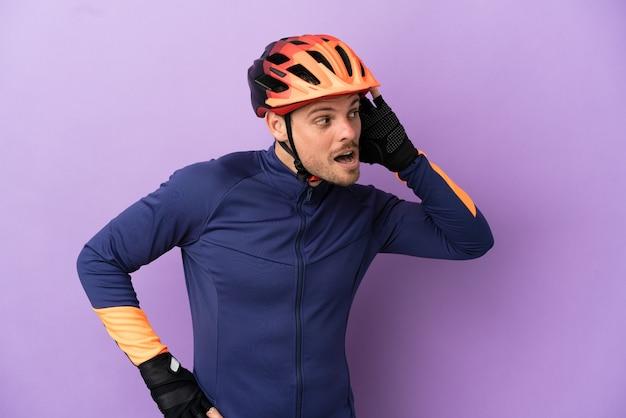 Молодой бразильский велосипедист изолирован на фиолетовом фоне, слушая что-то, положив руку на ухо