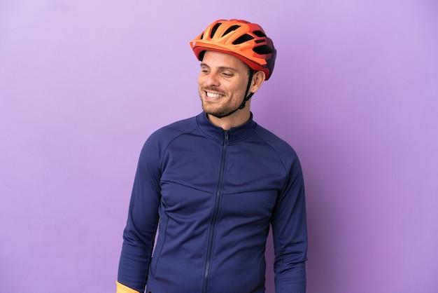 Молодой бразильский велосипедист мужчина изолирован на фиолетовом фоне, глядя в сторону и улыбаясь