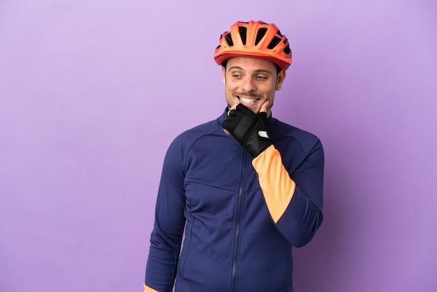 Молодой бразильский велосипедист мужчина изолирован на фиолетовом фоне, глядя в сторону и улыбаясь Premium Фотографии