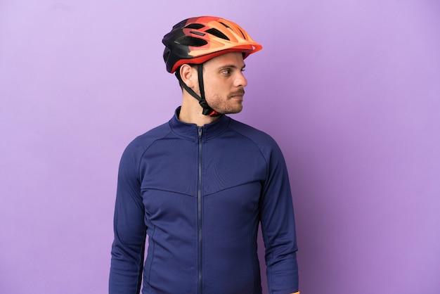 Молодой бразильский велосипедист мужчина изолирован на фиолетовом фоне, глядя в сторону