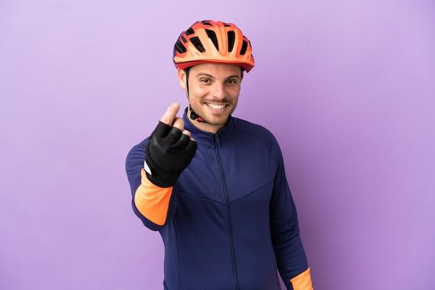 Молодой бразильский велосипедист мужчина изолирован на фиолетовом фоне, делая денежный жест