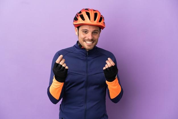 お金のジェスチャーを作る紫色の背景に分離された若いブラジルのサイクリストの男