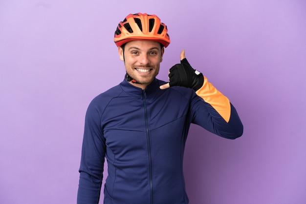 Молодой бразильский велосипедист человек изолирован на фиолетовом фоне, делая телефонный жест. перезвони мне знак