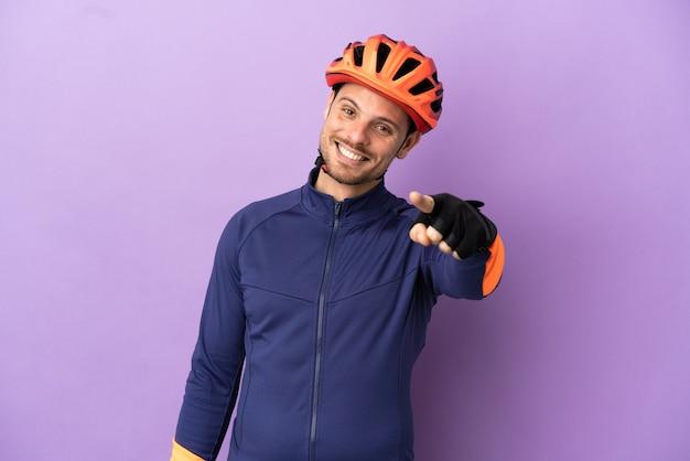 Молодой бразильский велосипедист изолирован на фиолетовом фоне, указывая вперед с счастливым выражением лица