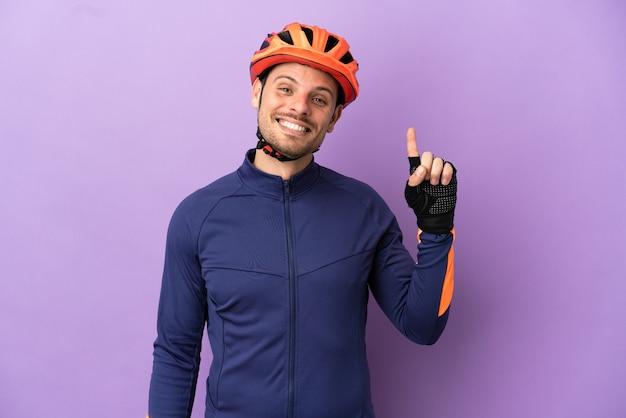 Молодой бразильский велосипедист изолирован на фиолетовом фоне, указывая на отличную идею