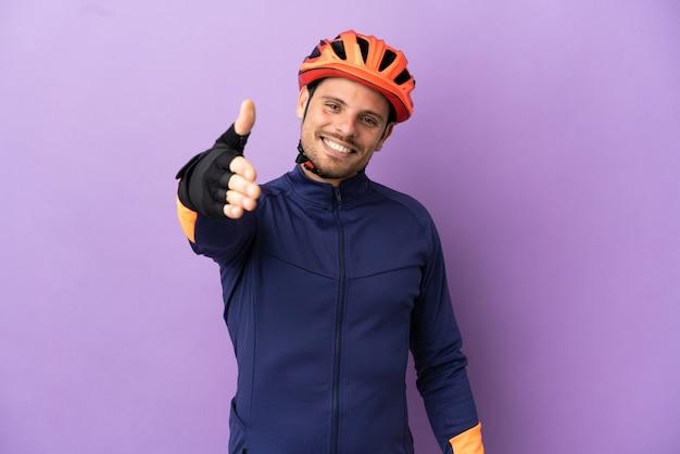 Молодой бразильский велосипедист изолирован на фиолетовом фоне, пожимая руку для заключения хорошей сделки