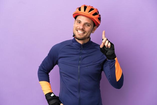 Молодой бразильский велосипедист, изолированные на фиолетовом фоне, показывает и поднимает палец в знак лучших