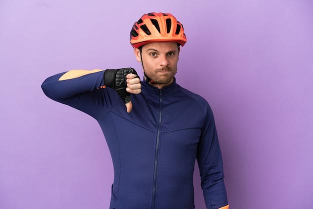 Молодой бразильский велосипедист изолирован на фиолетовом фоне, показывая большой палец вниз с отрицательным выражением лица