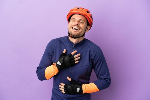 Молодой бразильский велосипедист мужчина изолирован на фиолетовом фоне, много улыбаясь