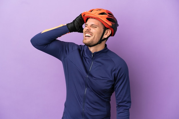 Молодой бразильский велосипедист человек изолирован на фиолетовом фоне, много улыбаясь