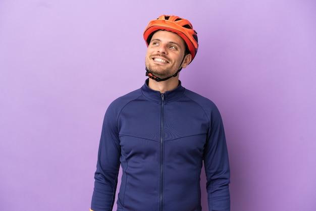 Молодой бразильский велосипедист мужчина изолирован на фиолетовом фоне, думая об идее, глядя вверх