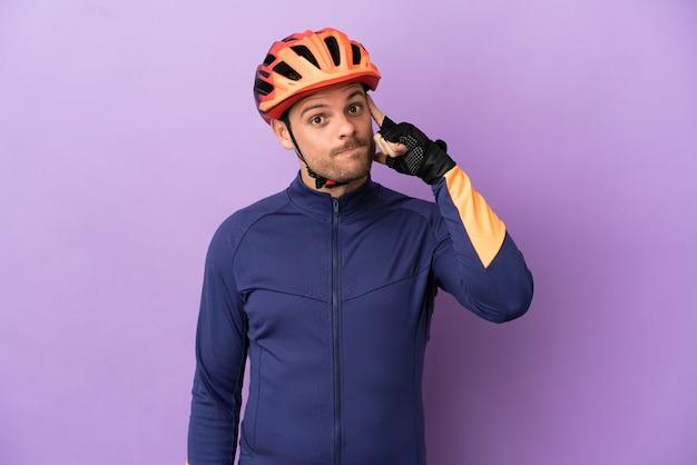 Молодой бразильский велосипедист человек изолирован на фиолетовом фоне, думая об идее
