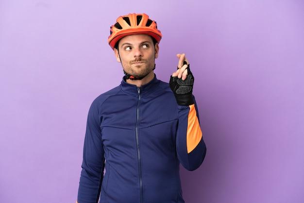 Молодой бразильский велосипедист изолирован на фиолетовом фоне со скрещенными пальцами и желает всего наилучшего