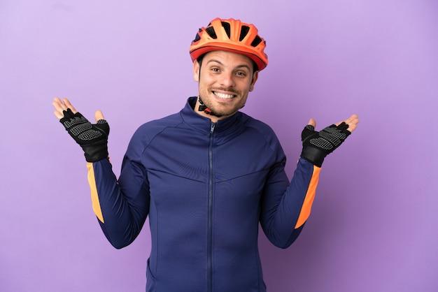 Молодой бразильский велосипедист изолирован на фиолетовом фоне с шокированным выражением лица