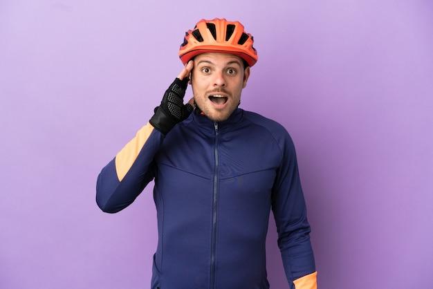 驚きとショックを受けた表情で紫色の背景に分離された若いブラジルのサイクリストの男