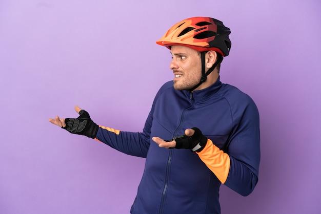 Молодой бразильский велосипедист изолирован на фиолетовом фоне с удивленным выражением лица, глядя в сторону