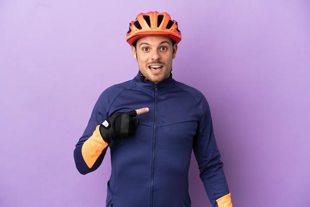 Молодой бразильский велосипедист изолирован на фиолетовом фоне с удивленным выражением лица