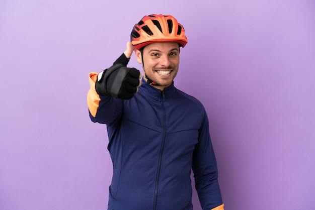 Молодой бразильский велосипедист изолирован на фиолетовом фоне с большими пальцами руки вверх, потому что произошло что-то хорошее
