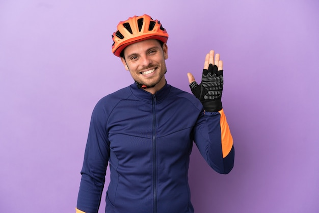 Young brazilian cyclist man isolated on purple background saluting with hand with happy expression