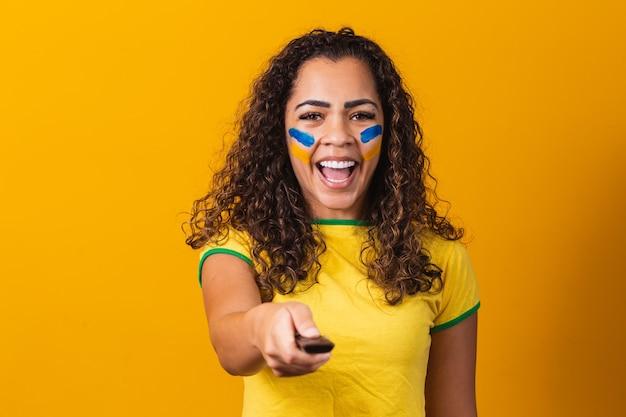 ブラジルの試合を観戦する準備ができている手にコントローラーを持つ若いブラジルのファンの女の子