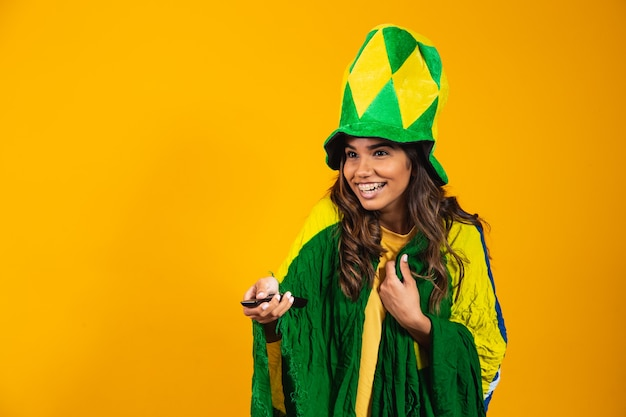 Молодая бразильская фанатка с контроллером в руке готова смотреть бразильскую игру