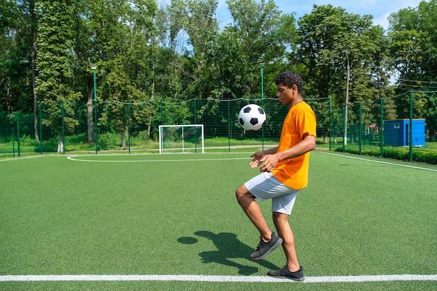 Молодой бразильский футболист на спортивном поле, пинающий и набивающий футбольный мяч на тренировке на открытом воздухе летним утром, вид сбоку