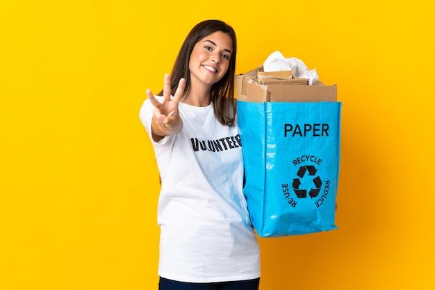 종이로 가득 찬 재활용 가방을 들고 젊은 브라질 소녀는 행복하고 손가락으로 세 세는 노란색 벽에 고립 된 재활용