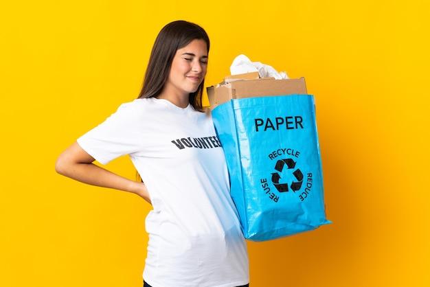 노력을 한 데 대한 요통으로 고통받는 노란색 벽에 고립 된 재활용 종이로 가득한 재활용 가방을 들고 젊은 브라질 소녀