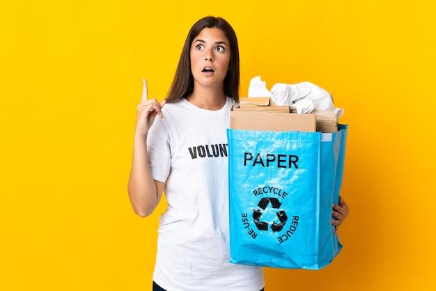 指を上に向けるアイデアを考えて黄色の壁に隔離されたリサイクルする紙でいっぱいのリサイクルバッグを保持している若いブラジルの女の子