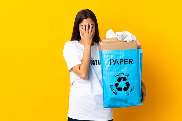 疲れて病気の表情で黄色の壁に隔離されたリサイクルする紙でいっぱいのリサイクルバッグを保持している若いブラジルの女の子