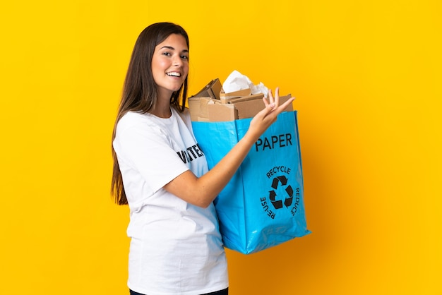 Young brazilian girl holding a recycling bag full of paper to recycle isolated