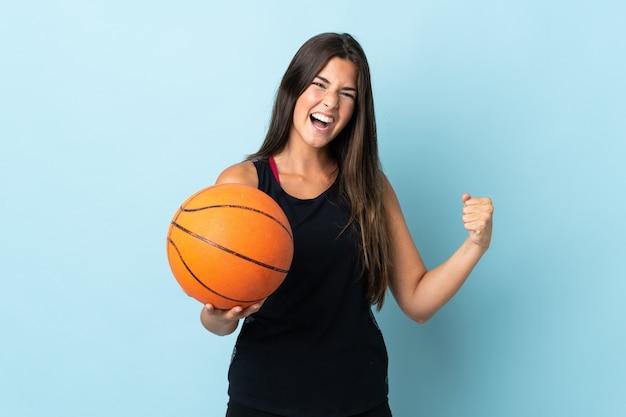 파란색 배경 농구에 고립 된 젊은 브라질 소녀