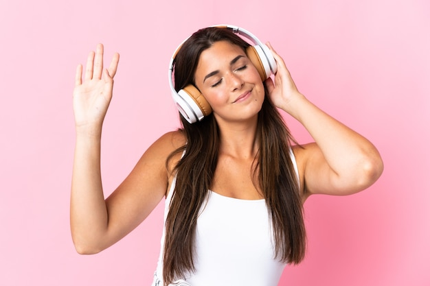 Молодая бразильская девушка изолирована на розовом, слушает музыку и танцует