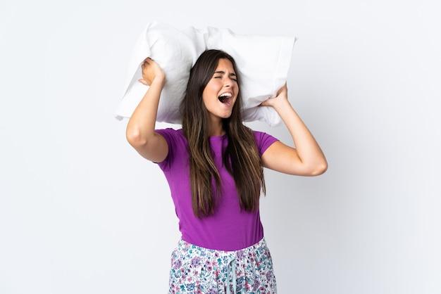 Young brazilian girl isolated on white wall in pajamas and holding a pillow stressed overwhelmed