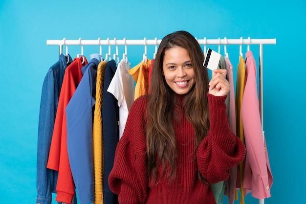 쇼핑백과 격리 된 파란색을 통해 저장소에 신용 카드로 젊은 브라질 여자