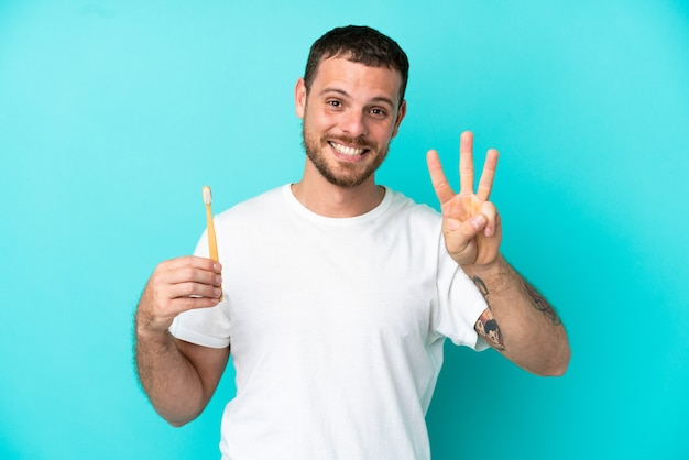 Young brazilian man brushing teeth isolated on blue background happy and counting three with fingers