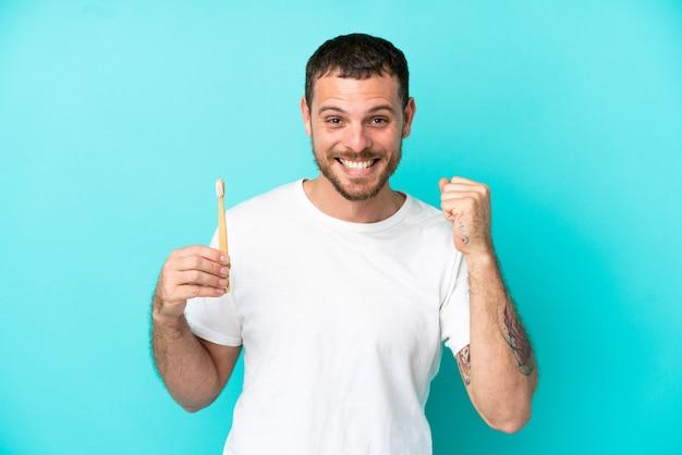 勝者の位置での勝利を祝う青い背景に分離された歯を磨く若いブラジル人男性