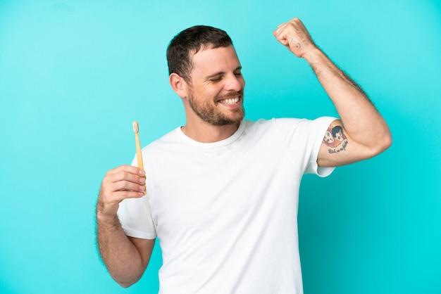 勝利を祝って青い背景で隔離の歯を磨く若いブラジル人男性