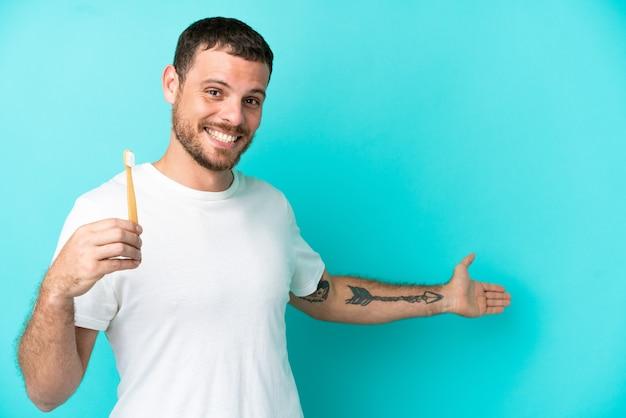 青の背景に分離された歯を磨く若いブラジル人男性が来て招待するために手を横に伸ばします