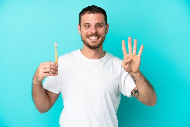 幸せな青い背景に分離された歯を磨き、指で4を数える若いブラジル人男性