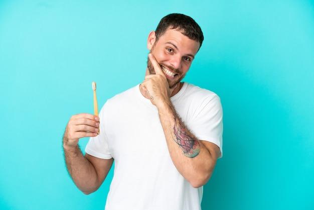 Молодой бразильский мужчина чистит зубы, изолированные на синем фоне, счастлив и улыбается