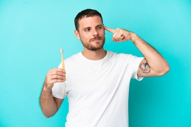 疑いと思考を持っている青い背景に分離された歯を磨く若いブラジル人男性