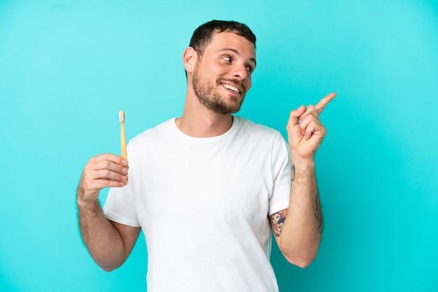 指を持ち上げながら解決策を実現しようと意図して青い背景で隔離の歯を磨く若いブラジル人男性