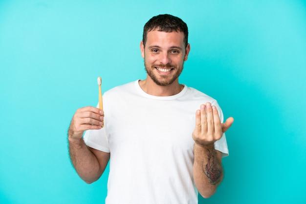 青の背景に分離された歯を磨く若いブラジル人男性が手で来るように誘う。あなたが来て幸せ Premium写真