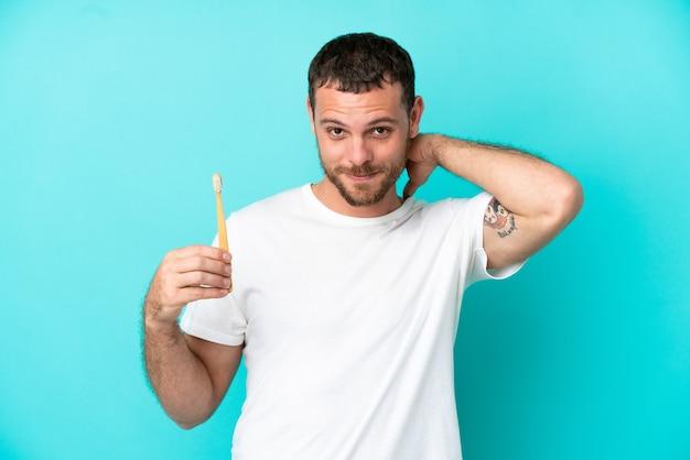 笑って青い背景で隔離の歯を磨く若いブラジル人男性