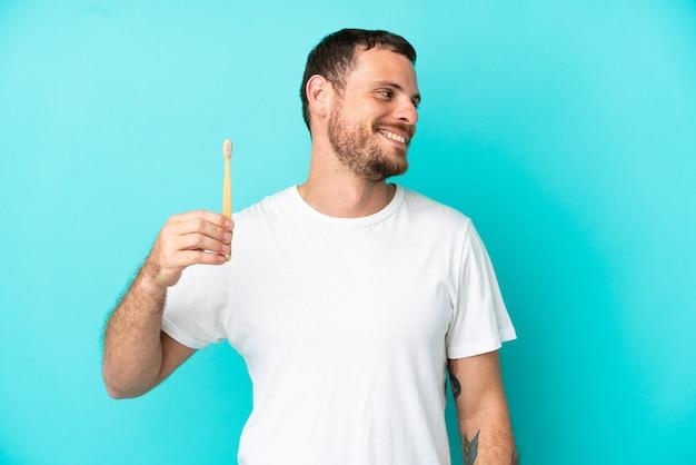 側面を見て青い背景で隔離の歯を磨く若いブラジル人男性