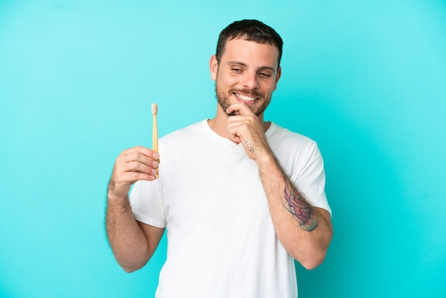横を見て笑っている青い背景で隔離の歯を磨く若いブラジル人男性
