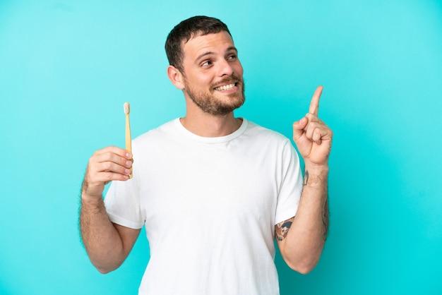 素晴らしいアイデアを指している青い背景に分離された歯を磨く若いブラジル人男性